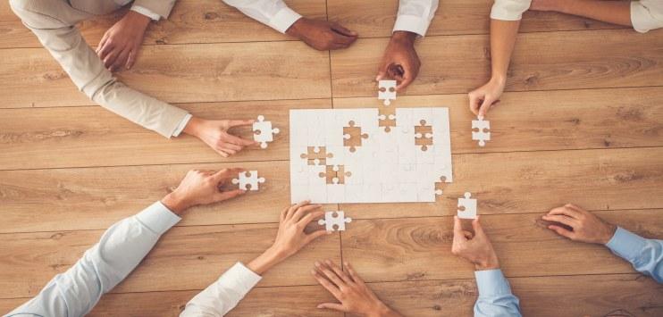 Imagem de pessoas montando um quebra-cabeças sobre uma mesa de madeira