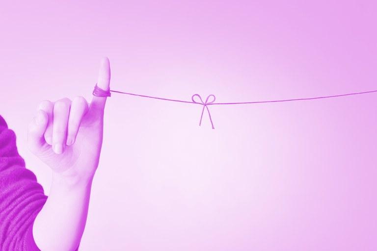 Uma mão com uma linha amarrada ao dedo, e esta linha segue, reta, até o outro lado da imagem