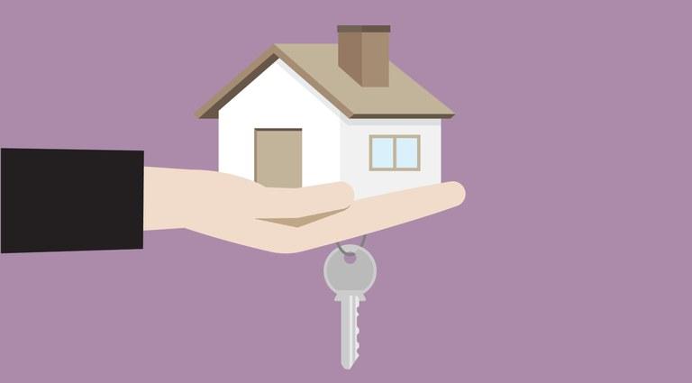 """Ilustração com uma mão """"segurando"""" uma casa e uma chave, fazendo referência à compra e venda de imóveis"""