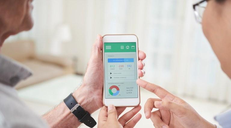 Imagem com mãos de duas pessoas (paciente e médica) e ambas segurando um celular. Na tela, dados estatísticos, como se fossem de saúde e as duas pessoas dialogando sobre esses dados.