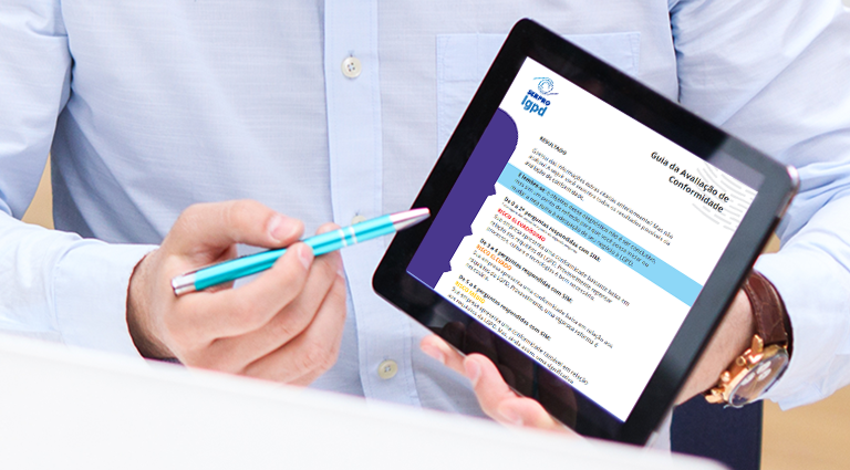 Imagem com mãos segurando um tablet. Na tela dele, uma das páginas da Avaliação de Conformidade disponibilizada no portal