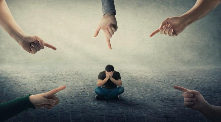Imagem com cinco mãos apontando para um homem, com as mãos no rosto, sentado ao centro
