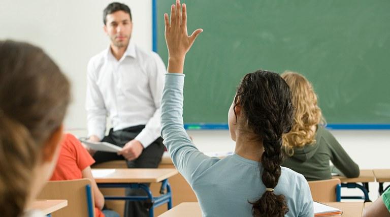 Foto com professor e alunos, em sala de aula. Uma aluna está com mão levantada, para fazer uma pergunta