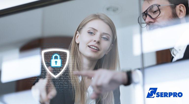 Foto com uma mulher e um homem conversando e apontando para uma parede de vidro no qual há um cadeado e algoritsmos, ícones que remetem a proteção de dados
