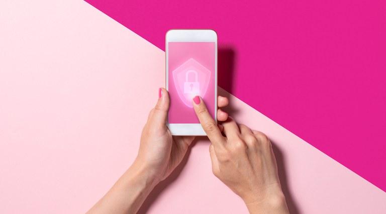 Foto de duas mãos segurando um celular. O dedo indicador da mão direita toca a tela do celular,  na qual tem o desenho de um cadeado.
