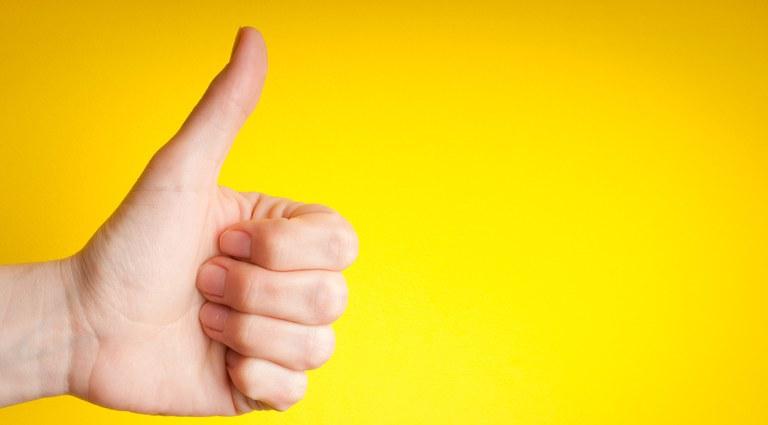 Mão com polegar levantado, e demais dedos fechados, remetendo à aprovação, consentimento