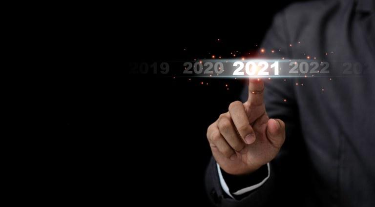 Mão de um homem num paletó toca e acende o número 2021, escrito de luz, tendo 2020 mais apagado à esquerda e 2022 à direita.