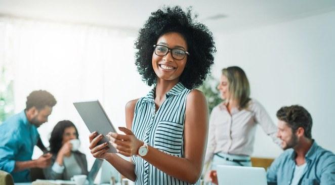Imagem de uma mulher sorridente, em destaque, segurando um notebook, com pessoas ao fundo, como se estivessem em reunião, conversando