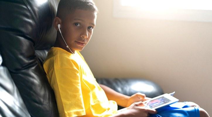 Foto um de menino, com blusa amarela e short azul, segurando um tablet e com um fone de ouvido