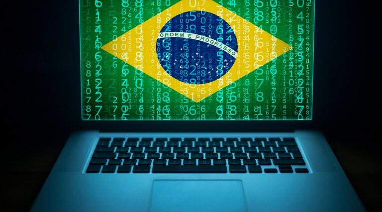 Ilustração com um notebook e, na tela dele, a bandeira do Brasil perpassada por códigos binários, remetendo à ANPD e à Lei Geral de Proteção de Dados Pessoais, do país
