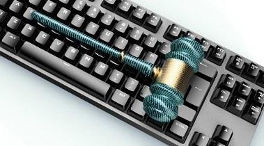 Foto com um teclado de computador e, acima dele, um martelo do modelo usado por juízes e juízas