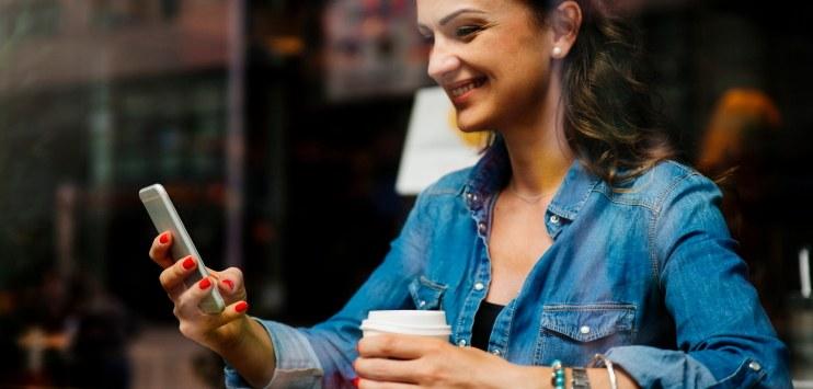 Mulher sorrindo ao manusear dispositivo eletrônico móvel (telefone celular)