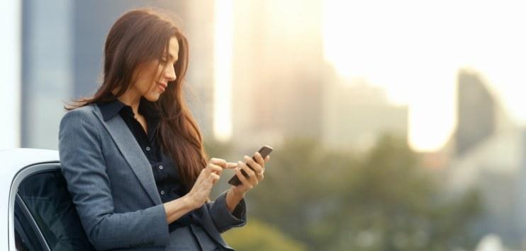 Mulher utilizando dispositivo móvel (telefone celular) ao ar livre