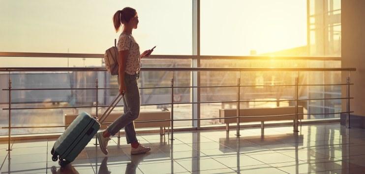 Mulher caminha em saguão do aeroporto com seu telefone celular em mãos