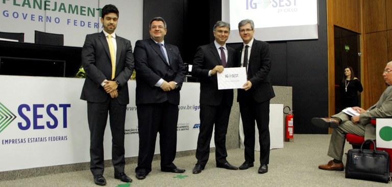 Diretor Iran Porto do Serpro está à direita da foto e recebe certificado das mãos do ministro do planejamento que está a sua direita. À esquerda, na foto, estão também em pé, dois representantes do Planejamento.