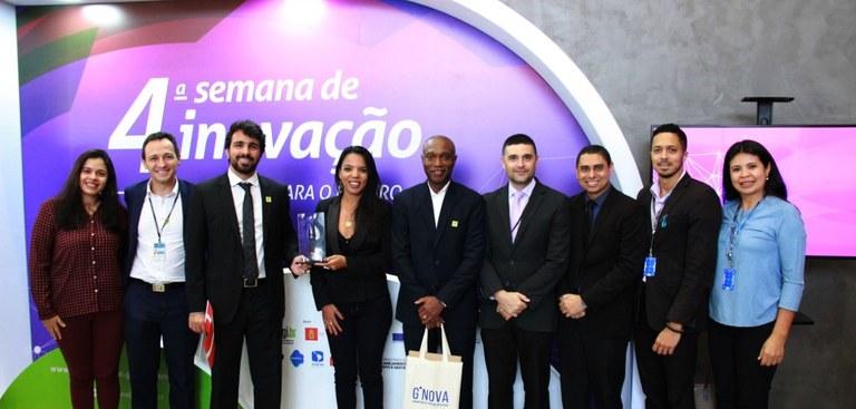 Nove profissionais do Serpro posam para foto em frente a banner com o nome da premiação