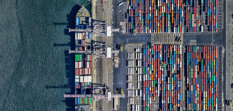 Imagem mostrando dezenas de containeres em um porto, ao lado de um navio atracado