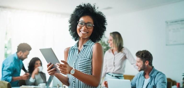Mulher negra olha para frente e sorri enquanto setgura um tablet. Atrás dela, dois homens e duas mulheres conversam numa mesa com um notebook aberto