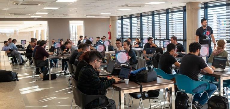 Vários participantes divididos em grupos em grandes mesas pensam nas soluções para o Hackathon