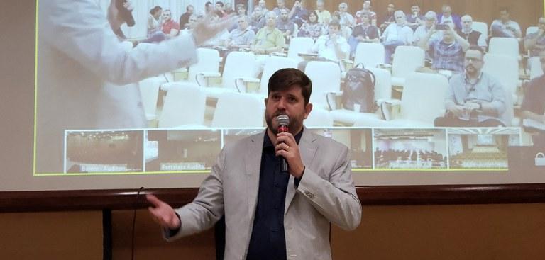 Superintendente de Operações do Serpro - Heitor Rapcinski - fala ao público no auditório - exibido na tela atrás dele