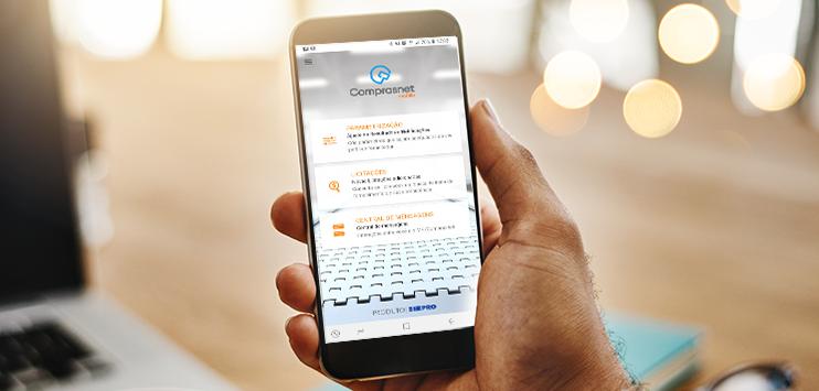 Imagem com uma mão segurando um celular. Na tela do celular, imagem do app Comprasnet Mobile e suas funcionalidades