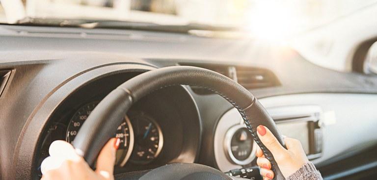 Carro visto por dentro. Mão feminina segura volante com brilho do sol ao lado.