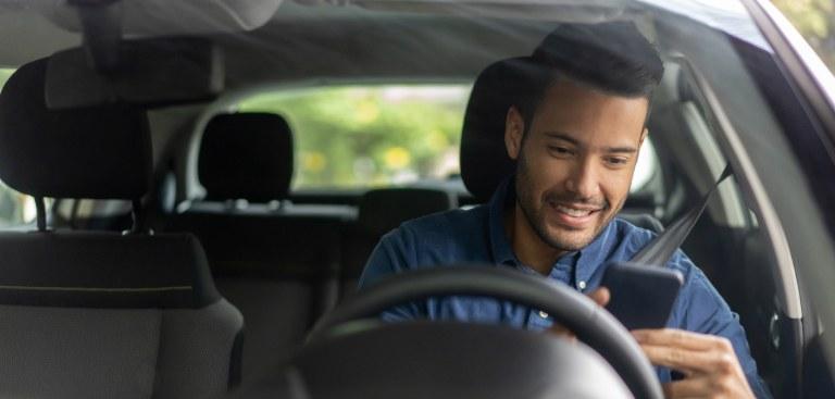 Foto com vista próxima do para-brisa de um carro. Há um homem no banco do motorista que sorri ao utilizar o celular.