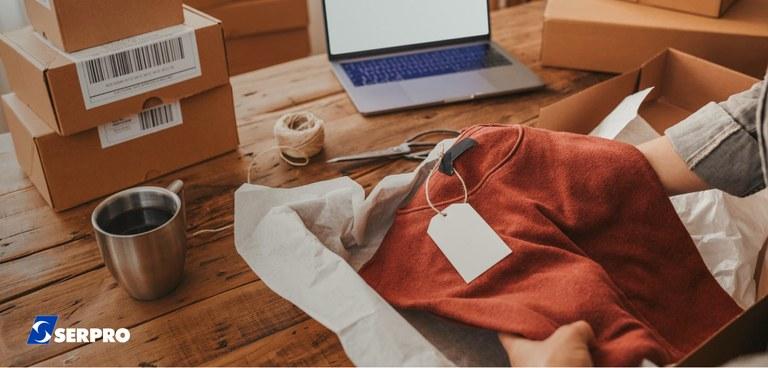 Funcionário de loja que vende pela internet embala uma blusa para entrega pelos Correios