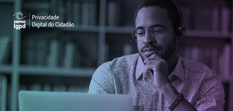 Homem trabalhando em um computador. No canto superior esquerdo da imagem foi aplicada a marca do LGPD PDC