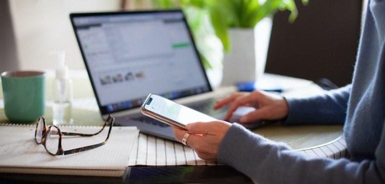 Foto de mulher trabalhando em casa usando um laptop enquanto lê uma mensagem de texto no celular. Na mesa, à esquerda, há um óculos sobre caderno e um potinho de álcool-gel e, ao fundo, há um jarro branco com planta verde desfocado.