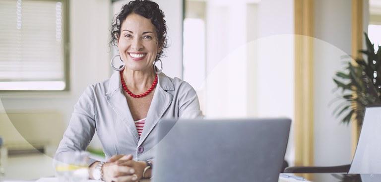Mulher sorrindo com as mãos apoiadas em uma mesa onde está posicionado um laptop