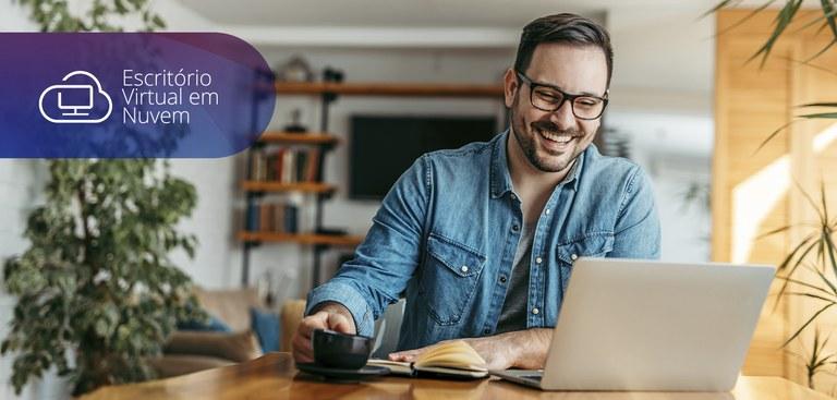Homem trabalhando em computador a partir de sua residência. No canto superior à esquerda está aplicada a marca do Escritório Virtual em Nuvem