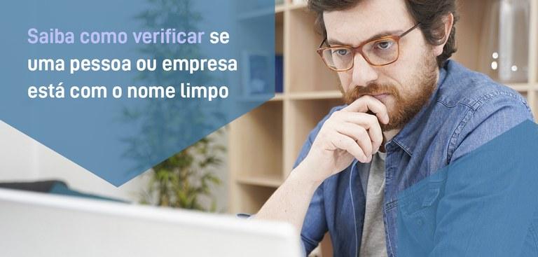Homem trabalhando em computador. Em destaque, a frase: Saiba como verificar se uma pessoa ou empresa está com o nome limpo