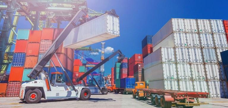 Foto de um pátio cheio de containers de variadas cores, um veículo com guindaste movimenta um container.