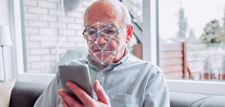 Idoso segura um celular que executa uma varredura de seu rosto. Ele está sentado em um sofá e atrás dele há uma janela pra uma área aberta da casa