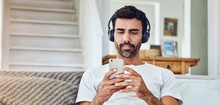 homem-no-sofa-usa-celular-com-fones-de-ouvido.jpg
