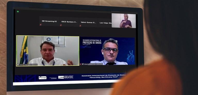 Mulher assiste à webconferência. No monitor, dois homens em telas diferentes dialogam
