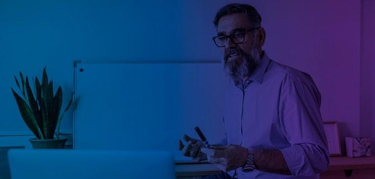 Fotografia de um professor dando aulas e interagindo com alunos por meio de um computador