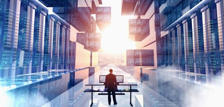 Ilustração estilizada de um ambiente tecnológico com a imagem de um centro de dados e nuvens na tonalidade azul. No centro da imagem um executivo em pé de costas está em frente a uma mesa operando um computador.
