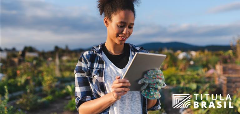 Foto de uma mulher que, em pé, numa área rural, olha para um tablet prata, segurando-o com uma luva florida de trabalho em uma das mãos. No canto inferior direito, a marca Titula Brasil